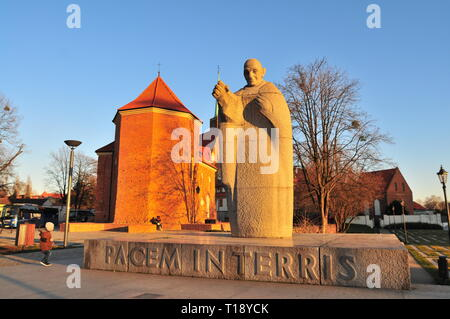 Pope John XXIII Granite Statue with Roman Catholic church of St. Marcin in the back. Wroclaw Ostrow Tumski. Poland - Stock Photo