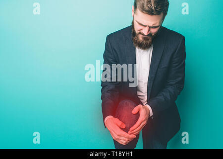 Man is holding on the knee. There is a pain. Guy is looking at it. The pain point is marked with red light. Isolated on blue background - Stock Photo