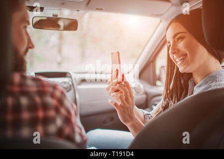 Young woman is taking picture of her man. She is looking at phone and smiling. She is doing that in car - Stock Photo
