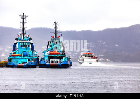 Two tug boats Vivax and Silex moored at Tollbodkaien in the port of bergen, Norway. Behind, high speed passenger catamaran Ekspressen on it's way out. - Stock Photo