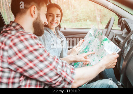 Young couple is sitting in car. They are holding a big map with their hands. Guy is pointing on map. Girl is looking at him and smiling - Stock Photo