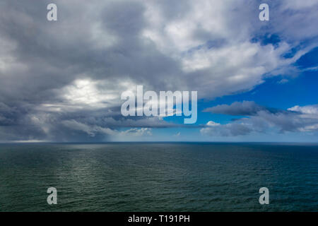 Calm flat ocean view with clouds and blue sky - Stock Photo