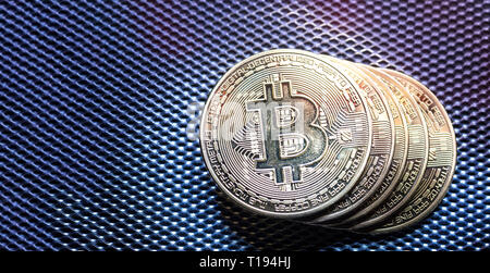 Top view of golden bit coins painted with light.Bitcoin digital currency and coin money stack on silver metallic dark background and surface - Stock Photo
