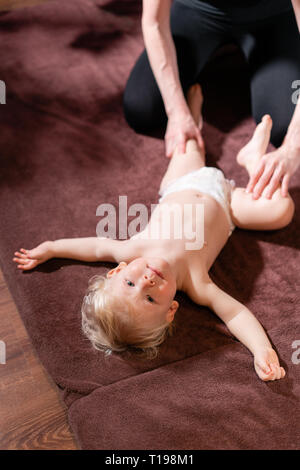 Baby massage. Mother or therapist makes massage to her baby at home. Health care and medicine concept. Blond boy - Stock Photo
