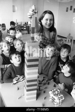 people, children, kindergarten / crib / approved school, kindergarten teacher putting doll on tower made of building toys, 1970s, Additional-Rights-Clearance-Info-Not-Available - Stock Photo