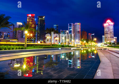Doha West Bay high rises at night reflecting in the water of downtown park. Lighting skyscrapers of Doha skyline in Qatar, Middle East, Arabian - Stock Photo