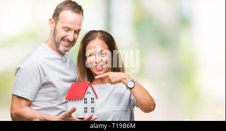 Middle age hispanic casual couple buying new house over isolated background very happy pointing with hand and finger - Stock Photo