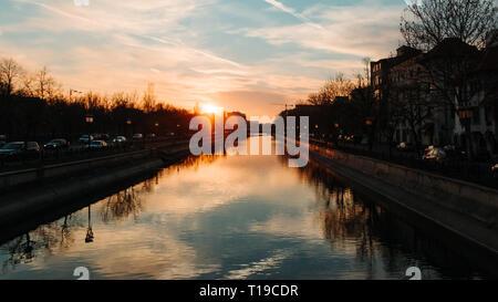 Sunset sun in Bucharest by the Dambovita river - Stock Photo