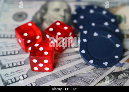 Red dice and casino gaming chips on US dollars bills. Concept of casino games, winning, gambling, luck or randomness - Stock Photo