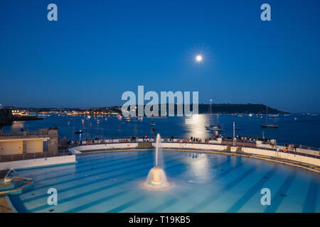 A moon going over Plymouth Tinside Lido at the National Firework Championships in Plymouth before a firework has set off. - Stock Photo
