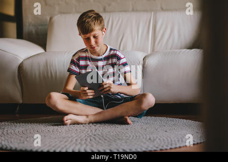 Young boy sitting on floor wearing earphones and playing video games on digital tablet. Boy in headphones playing online game on tablet at home. - Stock Photo