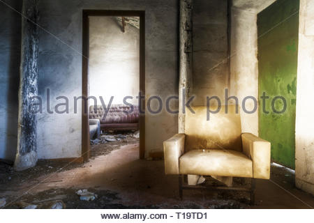 An old armchair in the room of an abandoned country house - Stock Photo