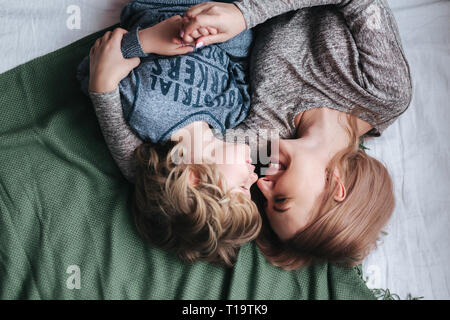 Beautiful woman and her cute little son are touching their noses and smiling
