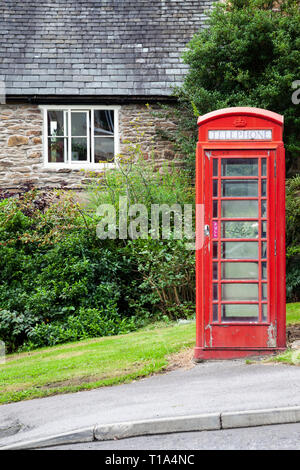 An old fashioned British red telephone box on next to a path in front of an old stone house - Stock Photo