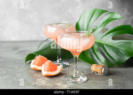 Drink grapefruit rosemary and ice in two elegant glass goblets on gray concrete background. Refreshing summer cocktail - Stock Photo