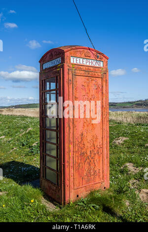 Old red telephone box near the beach at the village of Llansteffan on the Carmarthenshire coast on a bright sunny day. These are slowly becoming rarer - Stock Photo