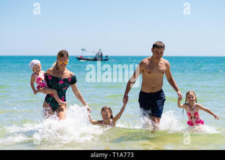 Group of happy children playing and splashing in the sea beach. Kids having fun outdoors. Summer vacation and healthy lifestyle concept. - Stock Photo