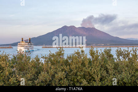 Active Vulcan Sakurajima and Kagoshima Ferry arriving the Port during summer sunset. Located in Kagoshima, Kyushu, South of Japan. Asia - Stock Photo