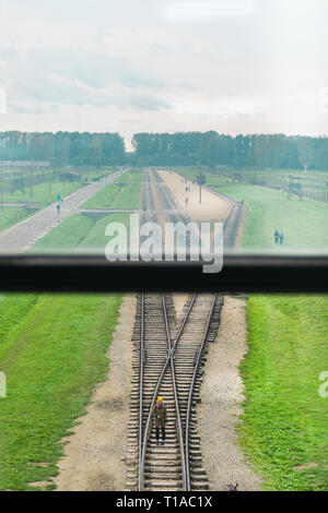 Oswiencim, Poland - September 21, 2019: Woman walk along the train line where the wagons arrived with the Birkenau prisoners.  - Stock Photo