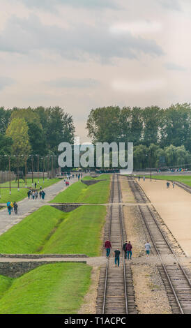 Oswiencim, Poland - September 21, 2019: Tourists walk along the train line where the wagons arrived with the Birkenau prisoners.  - Stock Photo