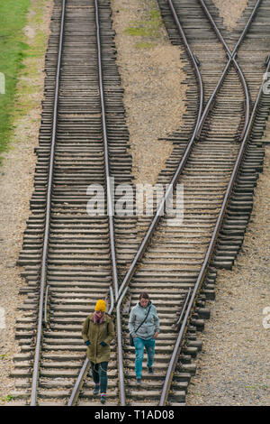 Oswiencim, Poland - September 21, 2019: Two womans walk along the train line where the wagons arrived with the Birkenau prisoners.  - Stock Photo