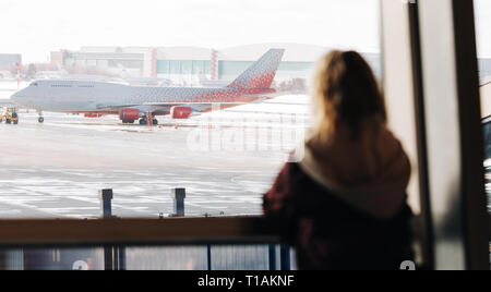 Image from back of blonde near window with plane flying by in afternoon. - Stock Photo