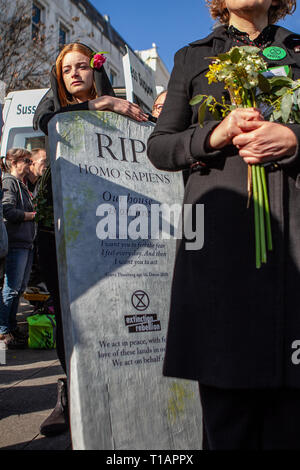 March 24, 2019 - righton, UK 24th March 2019. Protesters march through the centre of the city of Brighton holding a funeral procession for life on earth. The event was organised by the Brighton branch of Extinction Rebellion, which is a national movement fighting climate change and raising awareness of species extinction from the rise of the earth's temperature. The group believes that climate change is an unprecedented global emergency that need to be addressed before it becomes too late. A coffin was carried during the procession as a reminder of the deadly effects of climate change on wi - Stock Photo