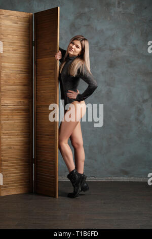 Cute girl in top, leather shorts and dense tights posing near folding screen - Stock Photo