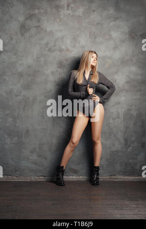 Pretty size plus model posing near folding screen over grunge abstract wall on background in closed body and rough boots - Stock Photo