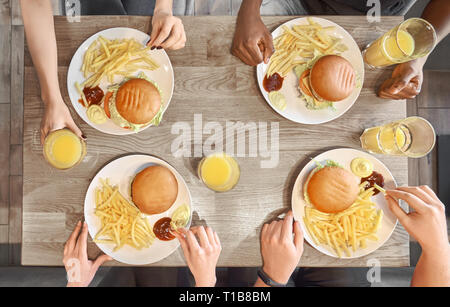 View from above of male and female hands on wooden table. Food served on white plates, hamburgers, french fries, sauce, mustard, orange juice in glasses. People eating fast food in cafe. - Stock Photo