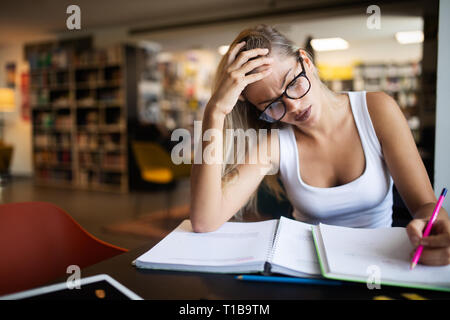 Student with desperate expression looking at her books - Stock Photo