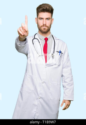 Young handsome doctor man wearing medical coat Pointing with finger up and angry expression - Stock Photo