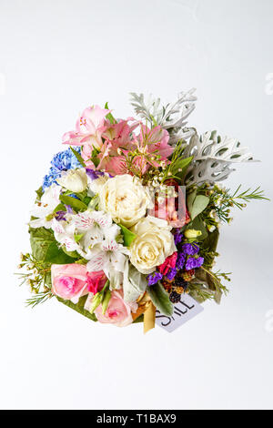 Photo from above of romantic bouquet of pink roses, lilies, green leaves with postcard isolated . - Stock Photo