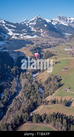 Stunning Aerial views over the a Swiss Alpine town and valley basin, surrounded by snow covered high mountain peaks and mountains. - Stock Photo