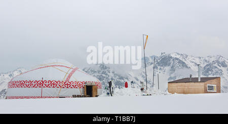 yurt standing in the snow with motorcycle in front of it, Mongolia - Stock Photo