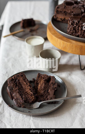 Pieces of chocolate cake on gray plate, whole cake on wooden stand, glass with milk on table. Concept of dessert table set - Stock Photo