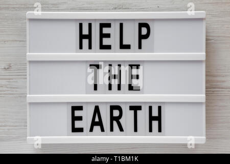 'Help the Earth' words on lightbox over white wooden background, top view. Flat lay, overhead, from above. - Stock Photo