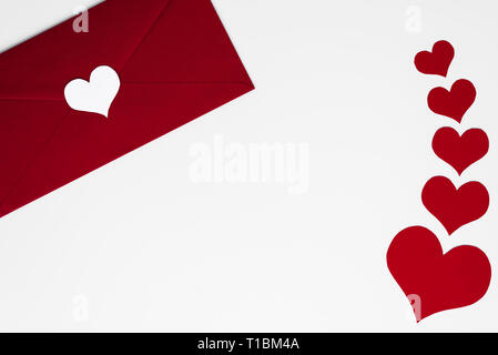 Concept of love letter in red envelope with white heart on. Romantic red hearts on white background with copy space. Happy Valentines. Mothers or Wome - Stock Photo