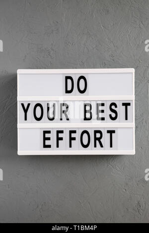 'Do your best effort' words on lightbox over concrete background, top view. Overhead, from above. Flat lay. - Stock Photo