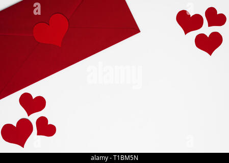 Concept of love letter in red envelope surrounded by romantic red hearts on white background with copy space. Happy Valentines. Mothers or Womens Day  - Stock Photo