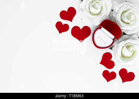 Set up from red hearts, white roses and open empty decorative box for engagement ring, all on white background with copy space for Happy Valentines. P - Stock Photo