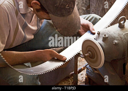 Man sharpening saw blades in wood carving workshop, Hotan, Xinjiang, China. - Stock Photo