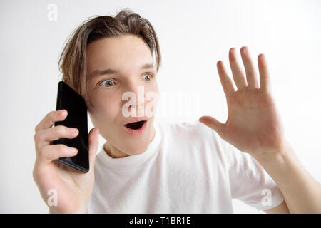 Wow. Its unbelievable. Shocking and breaking news. Young handsome teenager showing smartphone screen isolated on gray background. Human emotions, facial expression, advertising, education concept. - Stock Photo