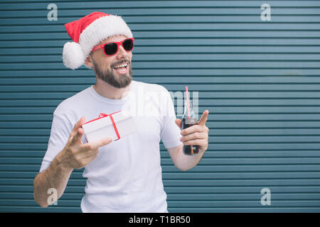 Nice man is standing and holding present in one hand and bottle of coke in another one. Also guy is pointing with finger. Man wears glasses and hat - Stock Photo