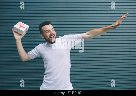 Brave man is ready to launch the present in air. Also guy is stretching another hand. He is smiling and very excited. Isolated on striped and blue - Stock Photo