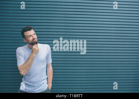 Thoughtful man is standing and looking to the right. He is holding hand on chin. Guy is looking up. Isolated on striped and blue background. - Stock Photo