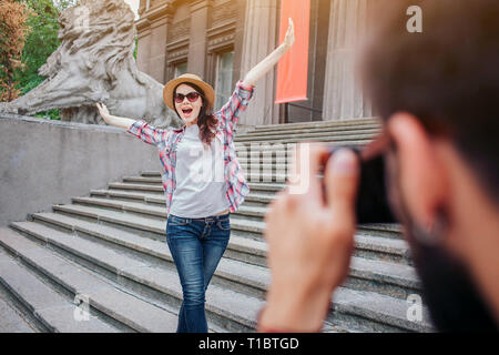 Young bearded man talking picture of happy woman. She poses on camera. Female tourist keep hands up and wears glasses. They stand on stairs. - Stock Photo