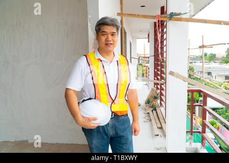 Asian professional engineer workering in house construction site for inspection of the cottage under construction - Stock Photo