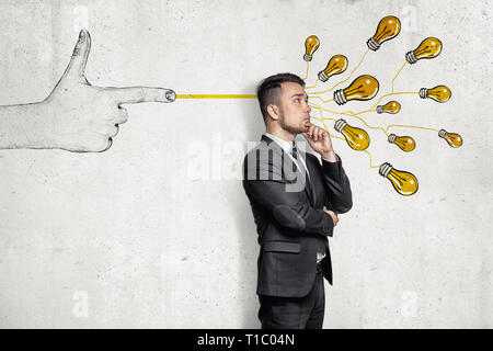 Businessman in half-turn, hand on chin, standing near wall with hand-drawn finger gun shooting bunch of yellow electirc bulbs at him.