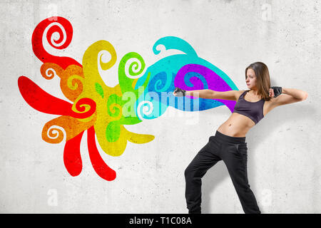Young attractive female dancer in black sleeveless crop top and sweatpants dancing near white wall with colorful abstract graffiti. - Stock Photo